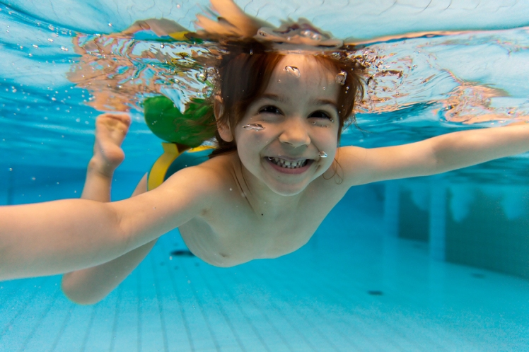 The girl smiles, swimming under water in the pool